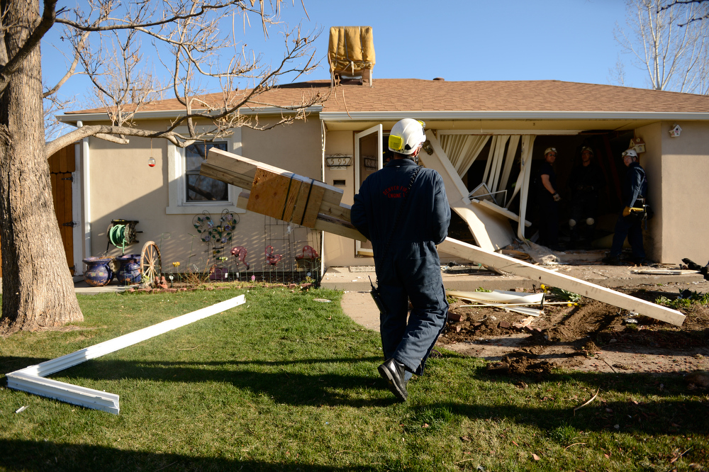 . Denver Fire works on shoring up a wall at a Denver home after an SUV crashed into the house, at the 5100 block of Gill Place in Denver, April 04, 2013. No one inside the home was hurt. (Photo By RJ Sangosti/The Denver Post)