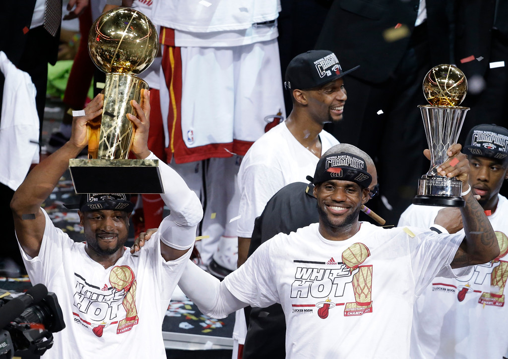 . The Miami Heat\'s Dwyane Wade, left, holds the Larry O\'Brien NBA Championship Trophy as  LeBron James holds his Bill Russell NBA Finals Most Valuable Player Award after Game 7 of the NBA basketball championship against the San Antonio Spurs, Friday, June 21, 2013, in Miami. The Miami Heat defeated the San Antonio Spurs 95-88 to win their second straight NBA championship. (AP Photo/Wilfredo Lee)