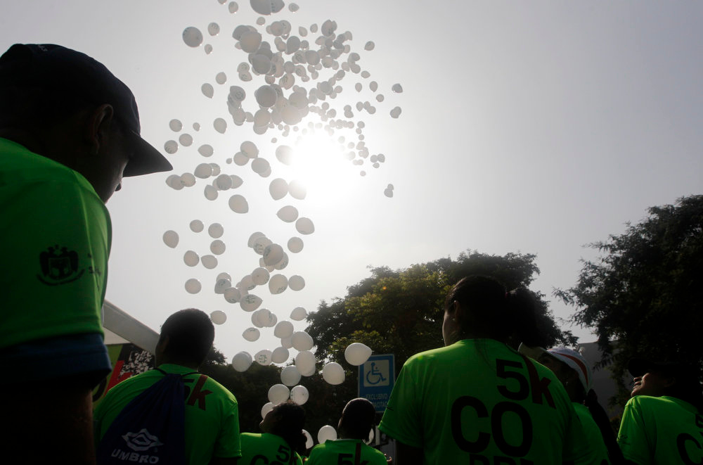 Description of . Runners observe the release of white balloons before the commencement of the 5K San Isidro Run in Lima, April 21, 2013. A minute of silence was observed by the runners before the race started, followed by a release of white balloons in tribute to the victims of the Boston Marathon Bombings. REUTERS/Mariana Bazo