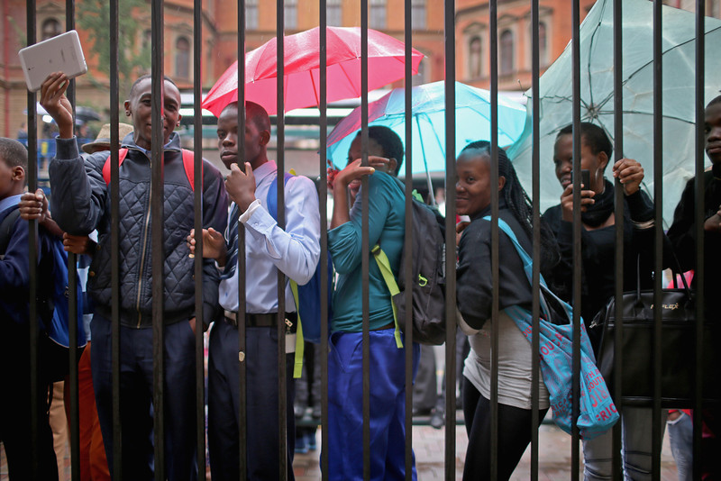 . South Africans try to get a glimpse of Oscar Pistorius as he leaves North Gauteng High Court at the end of the first day of his trial accused of the murder of his girlfriend Reeva Steenkamp on March 3, 2014 in Pretoria, South Africa. Olympic and Paralympic athlete Oscar Pistorius, aged 27, is accused of murdering his girlfriend Reeva Steenkamp. Pistorius denies the allegation claiming he mistook Steenkamp for an intruder inside their home on Valentines Day 2013.  (Photo by Christopher Furlong/Getty Images)