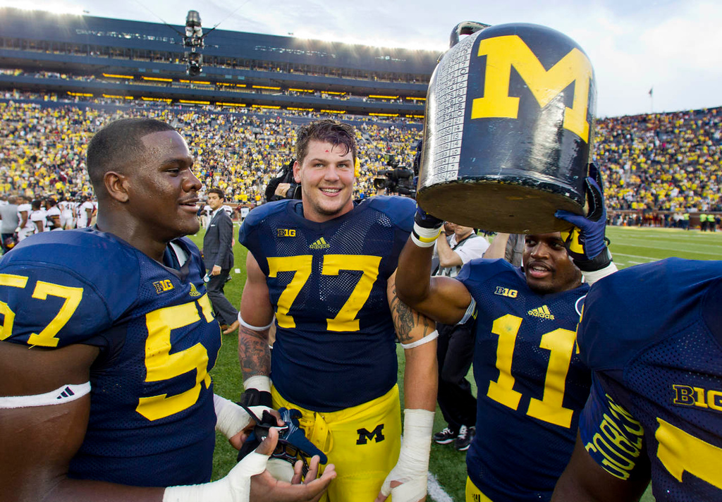 . Michigan defensive end Frank Clark (57), offensive lineman Taylor Lewan (77), and cornerback Courtney Avery (11) gather around the Little Brown Jug trophy after defeating Minnesota 42-13 in an NCAA college football game Saturday, Oct. 5, 2013, in Ann Arbor, Mich. (AP Photo/Tony Ding)