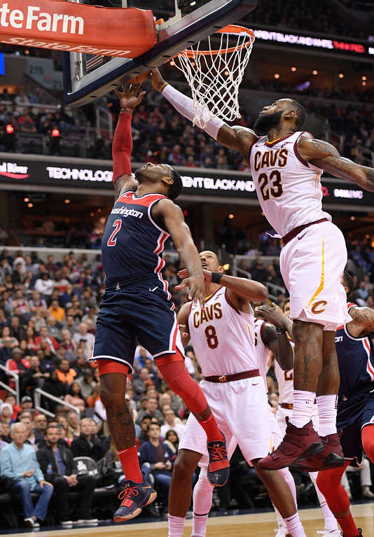 . Cleveland Cavaliers forward LeBron James (23) blocks Washington Wizards guard John Wall (2) during the second half of an NBA basketball game, Sunday, Dec. 17, 2017, in Washington. Cavaliers forward Channing Frye (8) looks on. (AP Photo/Nick Wass)