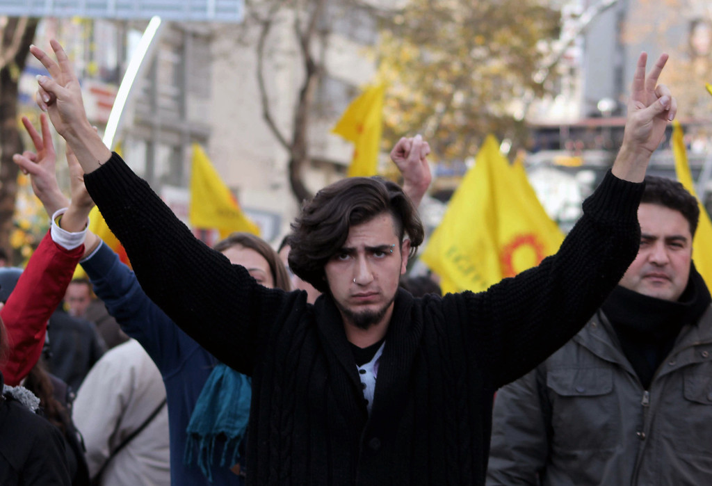 . A man flashes V-sign before riot police use water cannons and pepper gas to disperse thousands of Turkish teachers who were gathered to protest against the government\'s education and economic policies in Ankara, Turkey, Saturday, Nov. 23, 2013.(AP Photo)