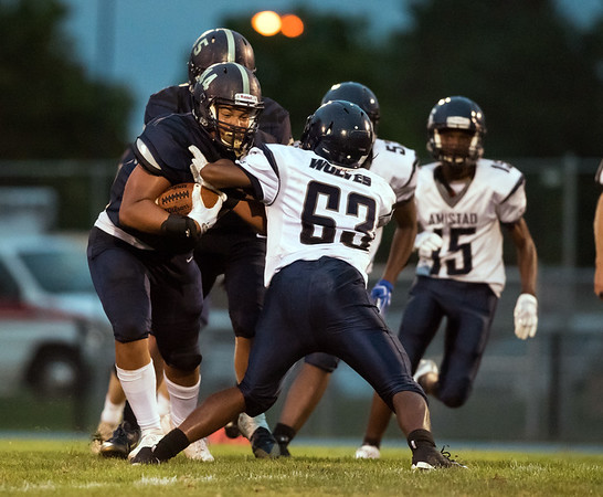 09/07/18 Wesley Bunnell | Staff Newington defeated Amsitad Academy on Friday night in Newington. Julian Mulero (44) with a carry.