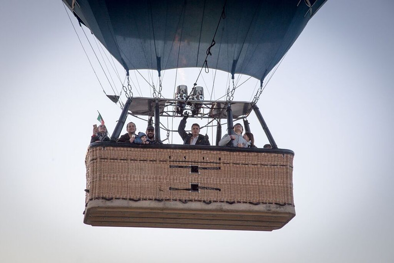 People waving from the basket of a hot air balloon