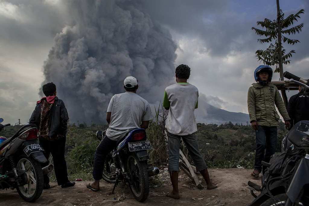 . People watch as Mount Sinabung spews pyroclastic smoke at Tiga Pancur village on October 13, 2014 in Berastagi, Karo district, North Sumatra, Indonesia.  (Photo by Ulet Ifansasti/Getty Images)