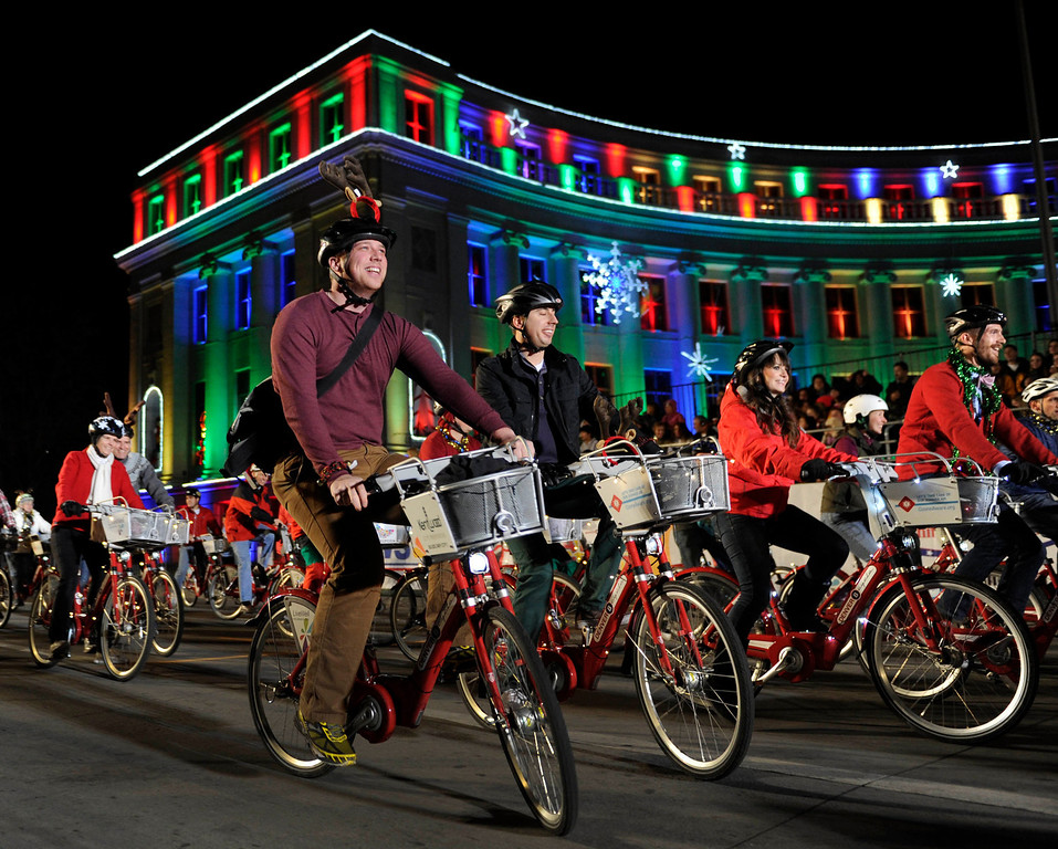 . Bicyclists promoting the city\'s bike sharing program rode down Bannock Street Friday night. The annual Parade of Lights filed past the illuminated City and County building in downtown Denver Friday night, November 30. 2012. The parade with 11 floats, 7 bands, 5 giant balloons and more lights than anyone could count, had enough holiday spirit to cheer even the biggest Scrooge. Karl Gehring/ The Denver Post