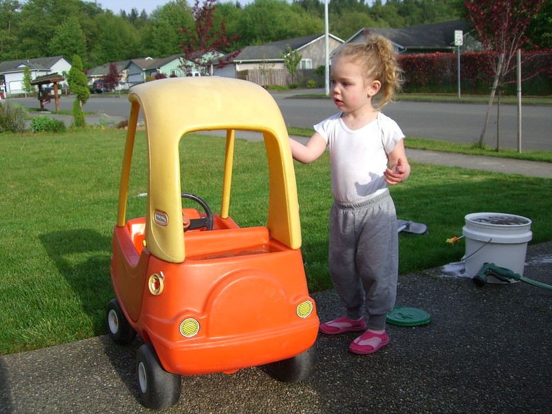 Washing her car while Daddy washes his.