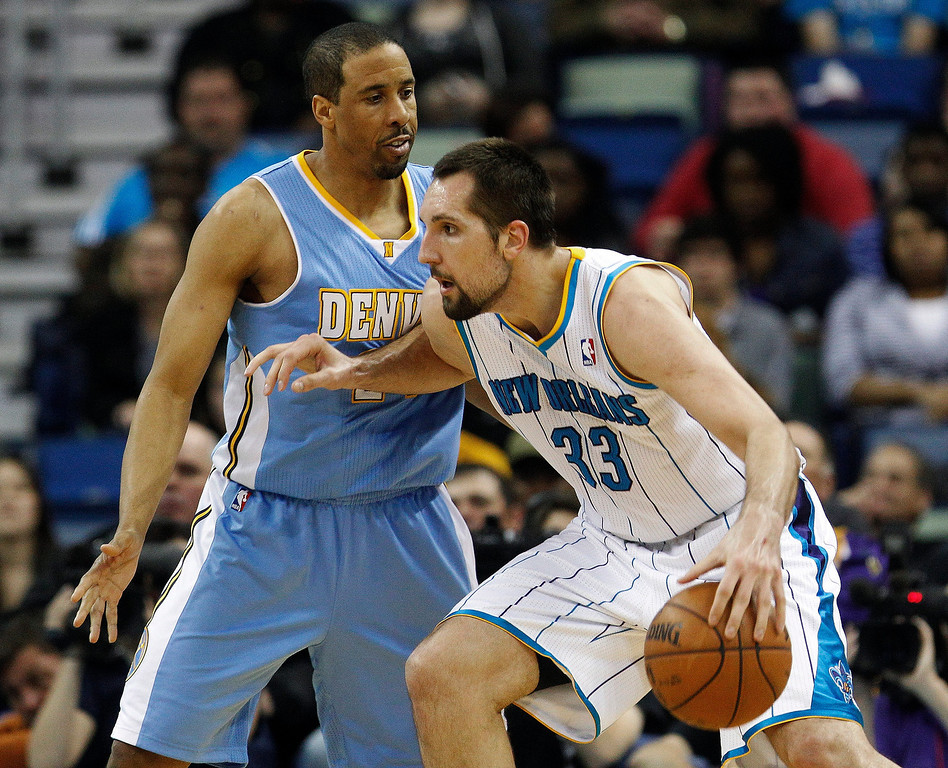 . New Orleans Hornets forward Ryan Anderson (33) fends off Denver Nuggets guard Andre Miller (24) in the second half of an NBA basketball game in New Orleans, Monday, March 25, 2013. The Hornets won 110-86. (AP Photo/Bill Haber)