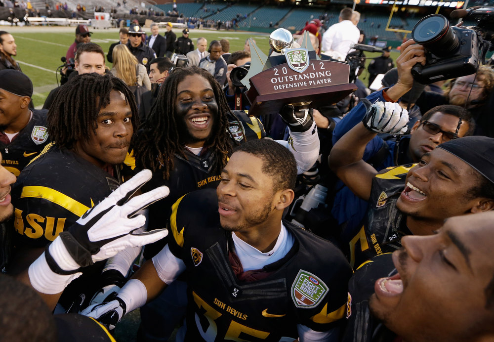 Description of . Will Sutton #90 of the Arizona State Sun Devils, who was named the defensive player of the game, celebrates with teammates after they beat the Navy Midshipmen in the Kraft Fight Hunger Bowl at AT&T Park on December 29, 2012 in San Francisco, California.  (Photo by Ezra Shaw/Getty Images)