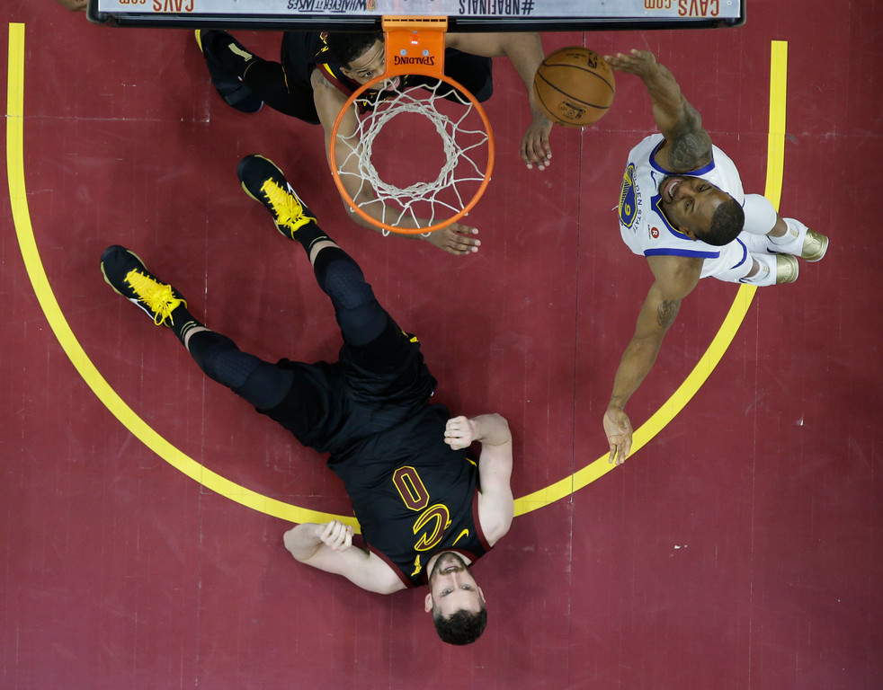 . Golden State Warriors\' Andre Iguodala shoots next to a fallen Cleveland Cavaliers\' Kevin Love during the second half of Game 3 of basketball\'s NBA Finals, Wednesday, June 6, 2018, in Cleveland. The Warriors defeated the Cavaliers 110-102 to take a 3-0 lead in the series. (AP Photo/Carlos Osorio, Pool)