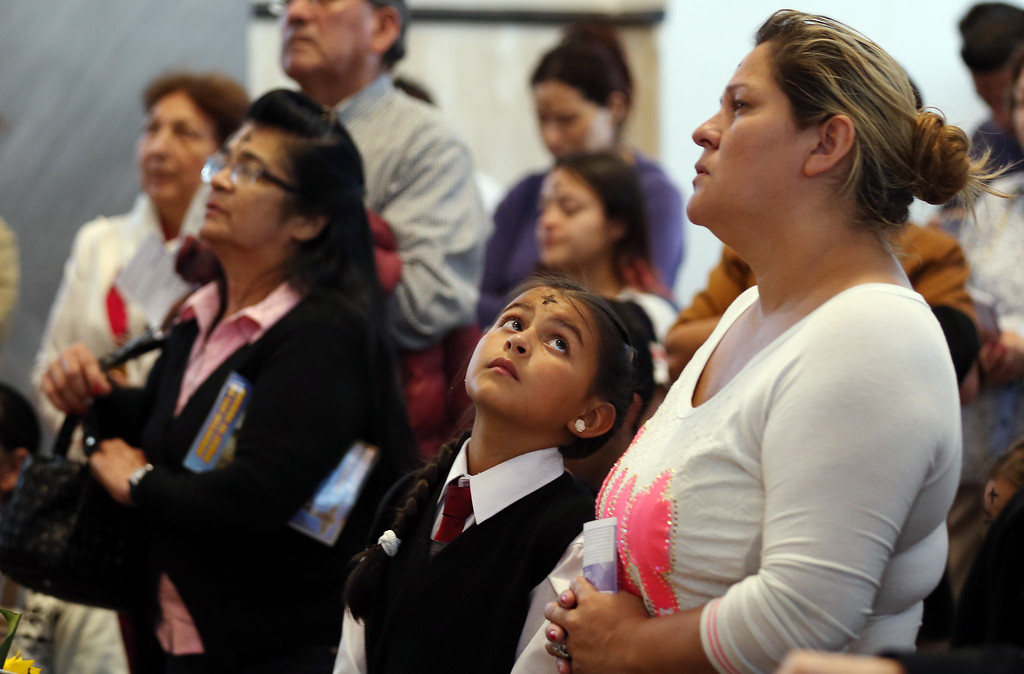 . A girl looks at the woman next to her during Mass for Ash Wednesday in Bogota, Colombia, Wednesday, Feb. 18, 2015. Ash Wednesday for Christians worldwide ushers in a period of penitence and reflection, known as the season of Lent, that leads up to Easter Sunday. (AP Photo/Fernando Vergara)