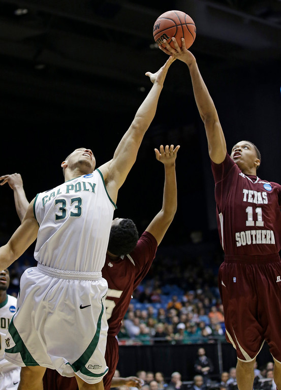 . Texas Southern guard Lawrence Johnson-Danner (11) and Cal Poly forward Chris Eversley (33) go for a rebound in the first half of a first-round game of the NCAA college basketball tournament on Wednesday, March 19, 2014, in Dayton, Ohio. (AP Photo/Al Behrman)