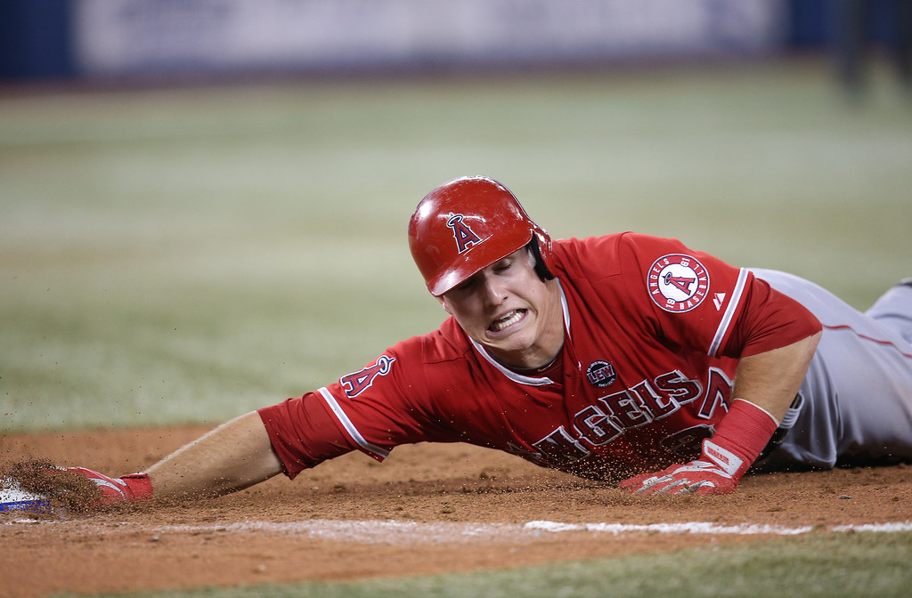 . TORONTO, CANADA - SEPTEMBER 11: Mike Trout #27 of the Los Angeles Angels of Anaheim dives back to first base on a pick-off attempt in the eighth inning during MLB game action against the Toronto Blue Jays on September 11, 2013 at Rogers Centre in Toronto, Ontario, Canada. (Photo by Tom Szczerbowski/Getty Images)