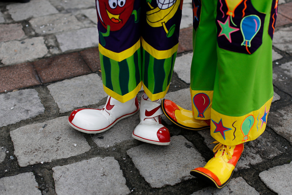. Wearing oversized shoes, a pair of clowns wait to participate in a laugh-a-thon at the the 17th International Clown Convention in Mexico City,Wednesday, Oct. 23, 2013. The laugh-a-thon was to protest violence in Mexico.  (AP Photo/Dario Lopez-Mills)