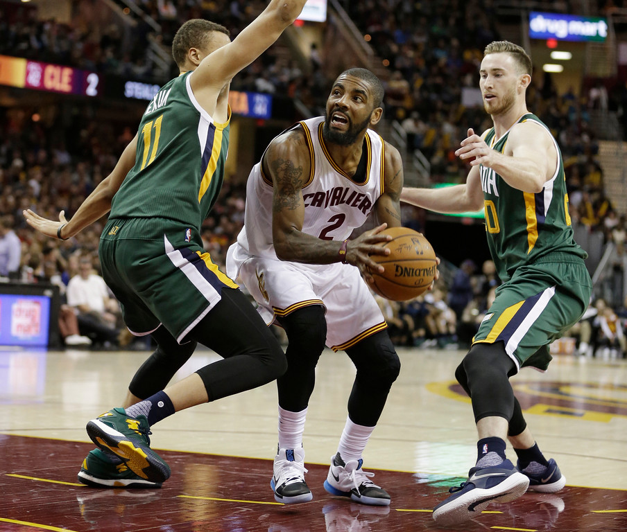 . Cleveland Cavaliers\' Kyrie Irving, center, drives against Utah Jazz\'s Dante Exum, left, and Utah Jazz\'s Gordon Hayward in the second half of an NBA basketball game, Thursday, March 16, 2017, in Cleveland. The Cavaliers won 91-83. (AP Photo/Tony Dejak)