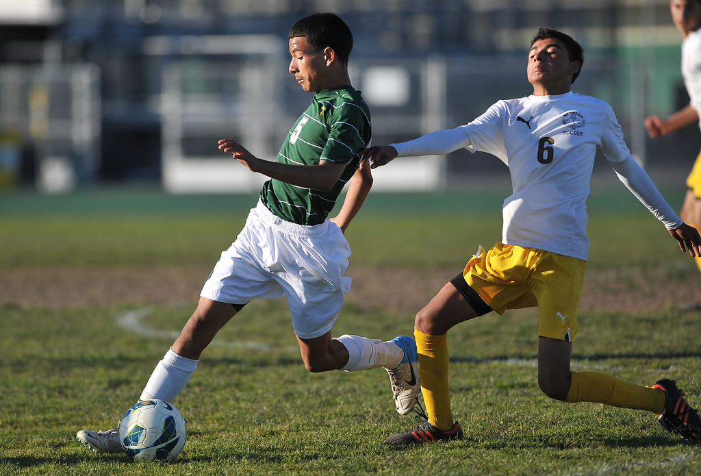 . 2/13/13 - Jeovann Alvarado of Narbonne High School takes the ball past Matthew Ocha of Kennedy during the L.A. City Section Division I playoffs. Narbonne won 1-0. Photo by Brittany Murray / Staff Photographer