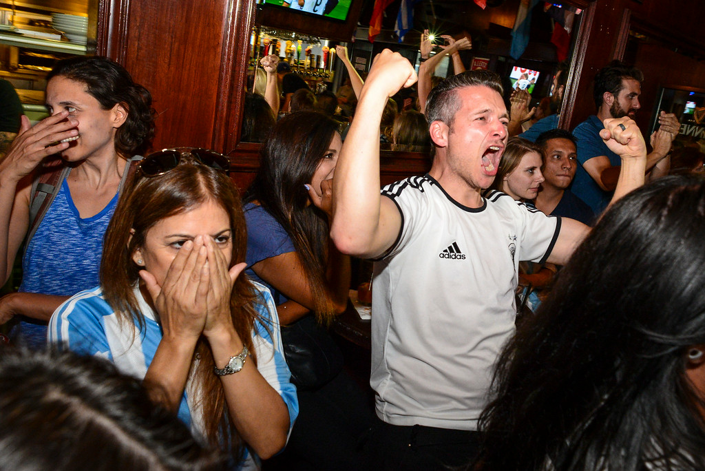 . Joanna Ryckman of Los Angeles, an Argentina fan, covers her eyes as German born Stefan Oriold, right, celebrates Germany\'s World Cup win at 33 Tap\'s Sport Bar in Hollywood, CA Sunday, July 13. 2014.( Photo by David Crane/Los Angeles Daily News )