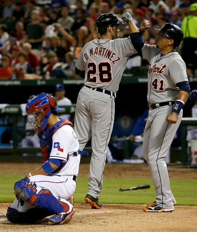 . Texas Rangers\' Robinson Chirinos kneels by the plate as Detroit Tigers\' J.D. Martinez (28) celebrates his two-run home run that scored Victor Martinez (41) in the seventh inning of a baseball game, Tuesday, June 24, 2014, in Arlington, Texas. The hit came off of Rangers starter -Colby Lewis in the 8-2 Tigers win. (AP Photo/Tony Gutierrez)