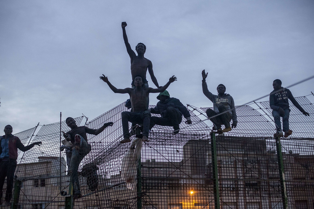 . Would-be immigrants react on a fence near Beni Enza, into the north African Spanish enclave of Melilla on March 28, 2014. Several hundreds people launched a dawn assault today to cross into the Spanish city, which lies on the northern tip of Morocco, and dozen made it across.      AFP PHOTO/ JOSE COLON/AFP/Getty Images