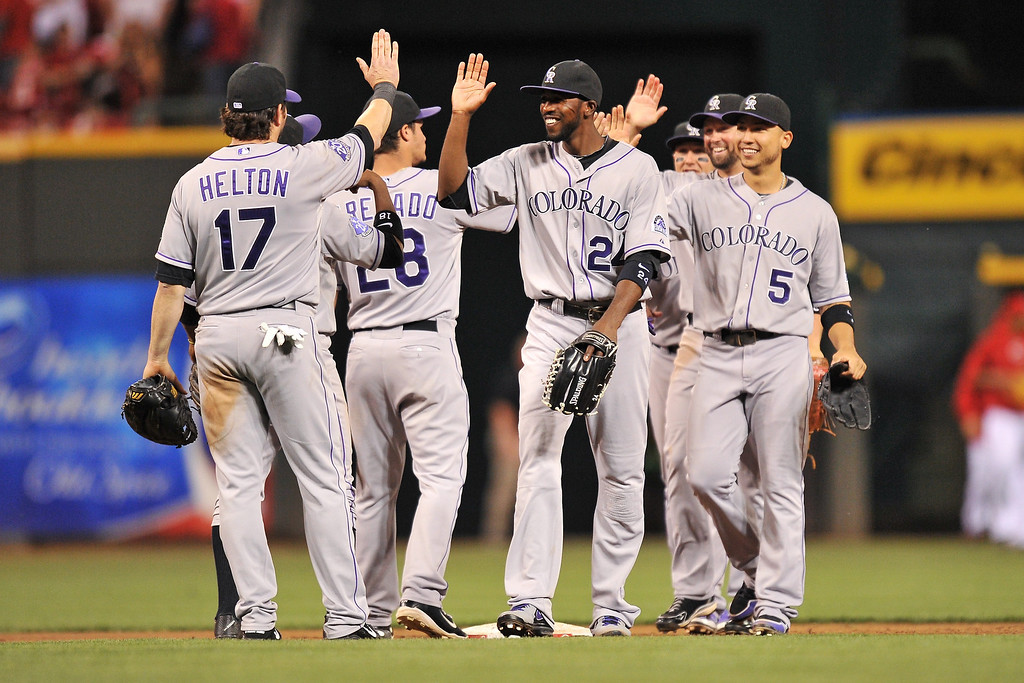 . Dexter Fowler #24 high-fives teammate Todd Helton #17 of the Colorado Rockies as they celebrate with the rest of the team a 5-4 win over the Cincinnati Reds at Great American Ball Park on June 4, 2013 in Cincinnati, Ohio.  (Photo by Jamie Sabau/Getty Images)