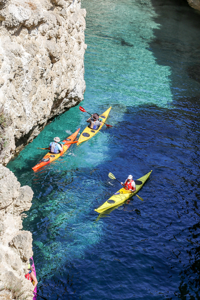 Three kayaks in the water in Milos. Part of a Greek Island cruise itinerary on Celestyal Cruises.