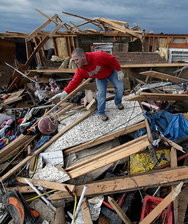 . Zac Woodcock salvages items from the rubble of a tornado-ravaged rental home which they own Tuesday, May 21, 2013, in Moore, Okla. A huge tornado roared through the Oklahoma City suburb Monday, flattening an entire neighborhoods and destroying an elementary school with a direct blow as children and teachers huddled against winds. (AP Photo/Charlie Riedel)