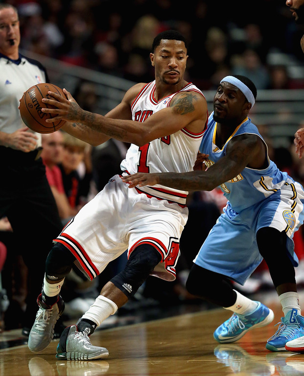 . Derrick Rose #1 of the Chicago Bulls works against Ty Lawson #3 of the Denver Nuggets during a preseason game at the United Center on October 25, 2013 in Chicago, Illinois. (Photo by Jonathan Daniel/Getty Images)