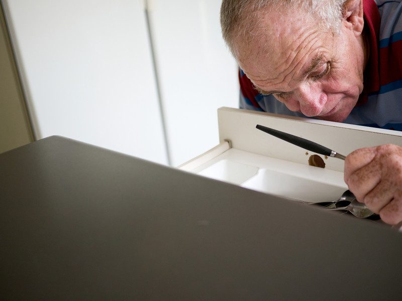 """This man, 66 years of age, is gathering cutlery in preparation of setting a table.  He has a disability and is photographed in his home.  This photo can be used to illustrate the importance of promoting engagement in meaningful activity.  This whole concept and practice has been referred to as Person-Centred Active Support and has extensive empirical evidence to support its importance in promoting a great quality of life for all people with a disability, """"irrespective of degree of disability or the presence of extra problems*  * Mansell, J., Beadle-Brown, J., Ashman, B., & Ockenden, J. (2004). Person-Centred Active Support. Pavilion Publishing (Brighton) Ltd.."""