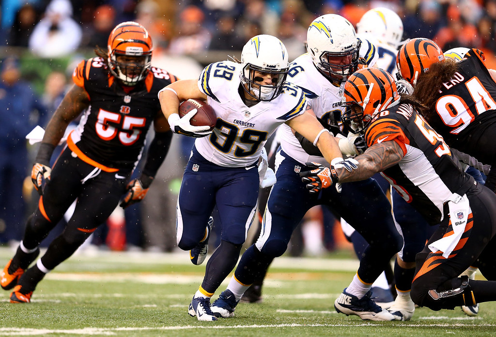 . Running back Danny Woodhead #39 of the San Diego Chargers carries the ball as middle linebacker Rey Maualuga #58 of the Cincinnati Bengals defends during a Wild Card Playoff game at Paul Brown Stadium on January 5, 2014 in Cincinnati, Ohio.  (Photo by Andy Lyons/Getty Images)