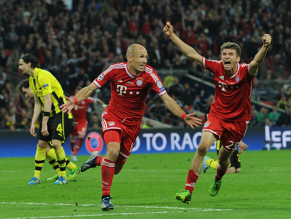 . Bayern Munich\'s Dutch midfielder Arjen Robben (L) celebrates scoring Bayern\'s second goal with Bayern Munich\'s German midfielder Thomas Mueller (R) during the UEFA Champions League final football match between Borussia Dortmund and Bayern Munich at Wembley Stadium in London on May 25, 2013  ANDREW YATES/AFP/Getty Images