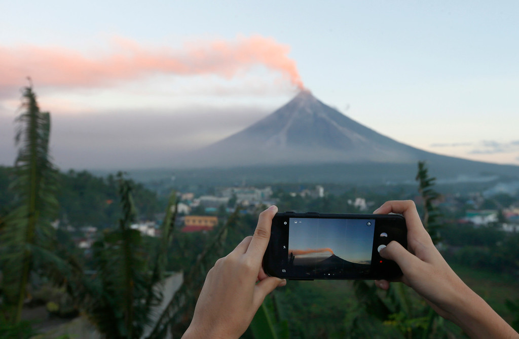 . A resident takes photos of Mayon volcano as it spews ash during a lull in its eruption Tuesday, Jan. 23, 2018 as seen from Legazpi city, Albay province, around 340 kilometers (200 miles) southeast of Manila, Philippines. The Philippines\' most active volcano ejected a huge column of lava fragments, ash and smoke in another thunderous explosion at dawn Tuesday, sending thousands of villagers back to evacuation centers and prompting a warning that a violent eruption may be imminent. (AP Photo/Bullit Marquez)