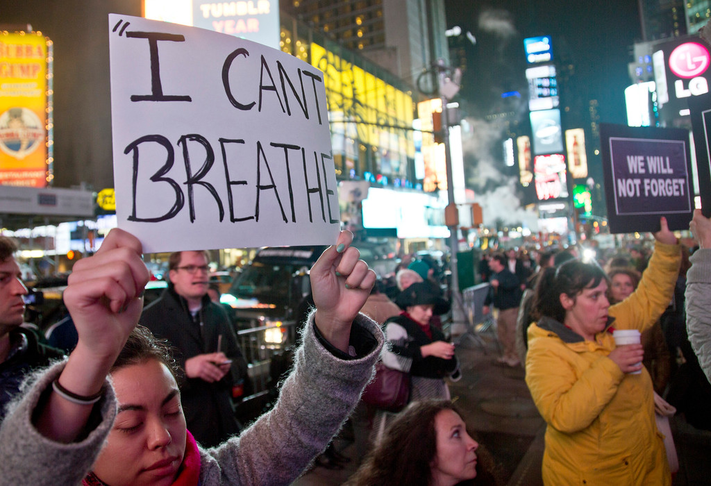. Protesters in Times Square carry signs in reaction to a non indictment against a police officer in the death of Eric Garner, Wednesday Dec. 3, 2014 in New York.  (AP Photo/Bebeto Matthews)