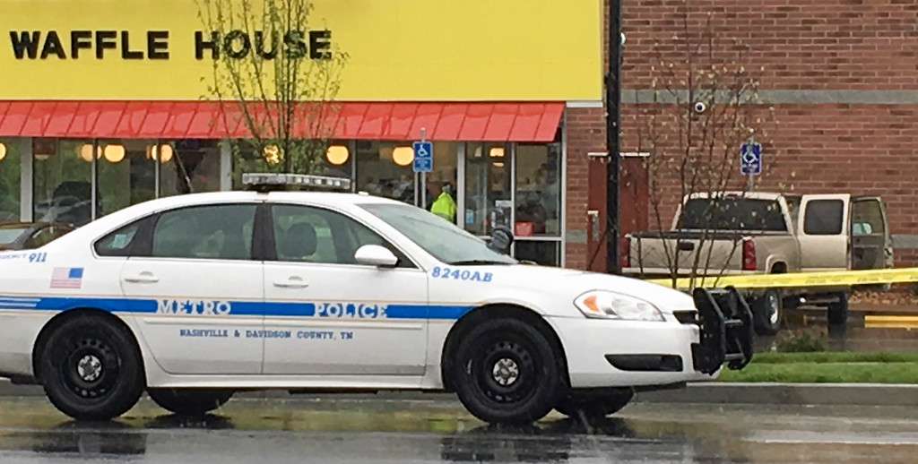. A police vehicle sits outside a Waffle House restaurant in Nashville, Tenn., Sunday, April 22, 2018. A man wearing nothing but a coat stormed the restaurant before dawn Sunday and shot several people to death, according to police, who credited a customer with saving lives by wresting a weapon away from the gunman. (AP Photo/Sheila Burke)