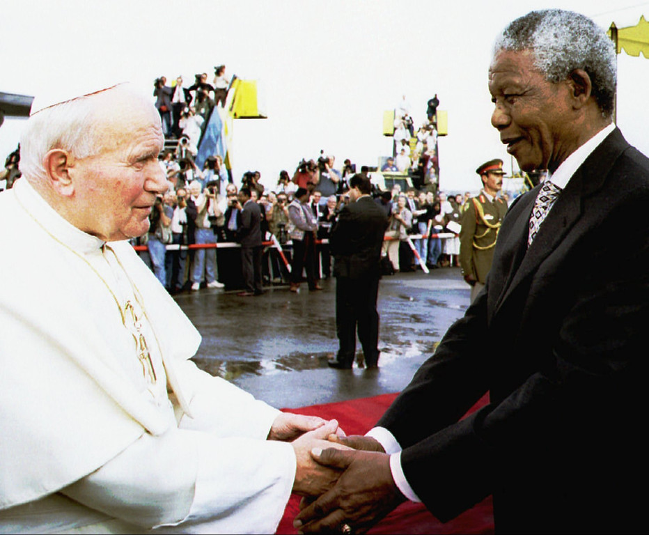. Pope John Paul II is welcomed by South African President Nelson Mandela, right, upon his arrival at Johannesburg airport at the start of his first official visit to South Africa Saturday September 16, 1995. (AP Photo/Pool)