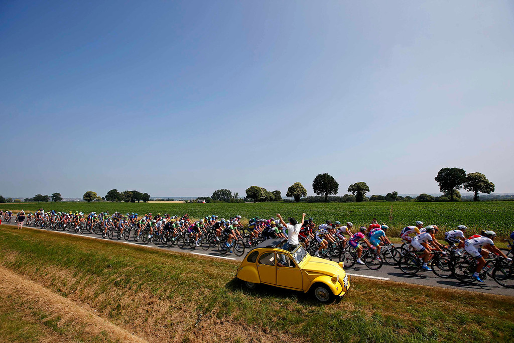 . A spectator standing in a yellow Citroen 2CV car waves as the pack of riders cycles on its way during the twelfth 218km stage of the centenary Tour de France cycling race from Fougeres to Tours July 11, 2013.    REUTERS/Eric Gaillard