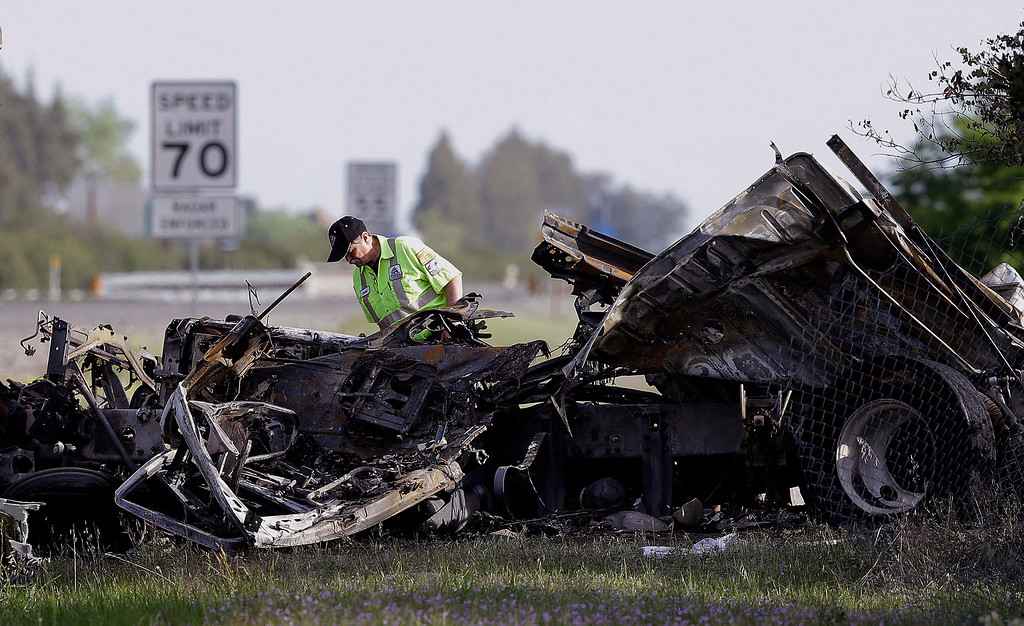 . A worker looks over the demolished cab of FedEx truck that crashed into a tour bus on Interstate 5 Thursday in Orland, Calif., Friday, April 11, 2014. At least ten people were killed and dozens injured in the fiery crash between the truck and a bus carrying high school students on a visit to a Northern California College. (AP Photo/Jeff Chiu)