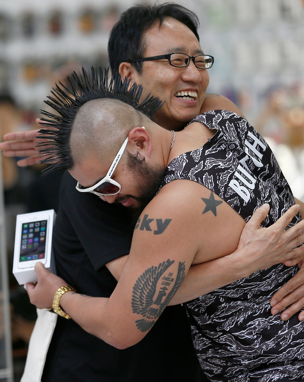 . Ken Miyauchi, left, vice president of Softbank, Japanese mobile phone company hugs the first customer of iPhone 6 during a ceremony to mark the first day of sales of the new Apple iPhone 6 and 6 Plus at a store  in Tokyo Friday, Sept. 19, 2014. (AP Photo/Shizuo Kambayashi)