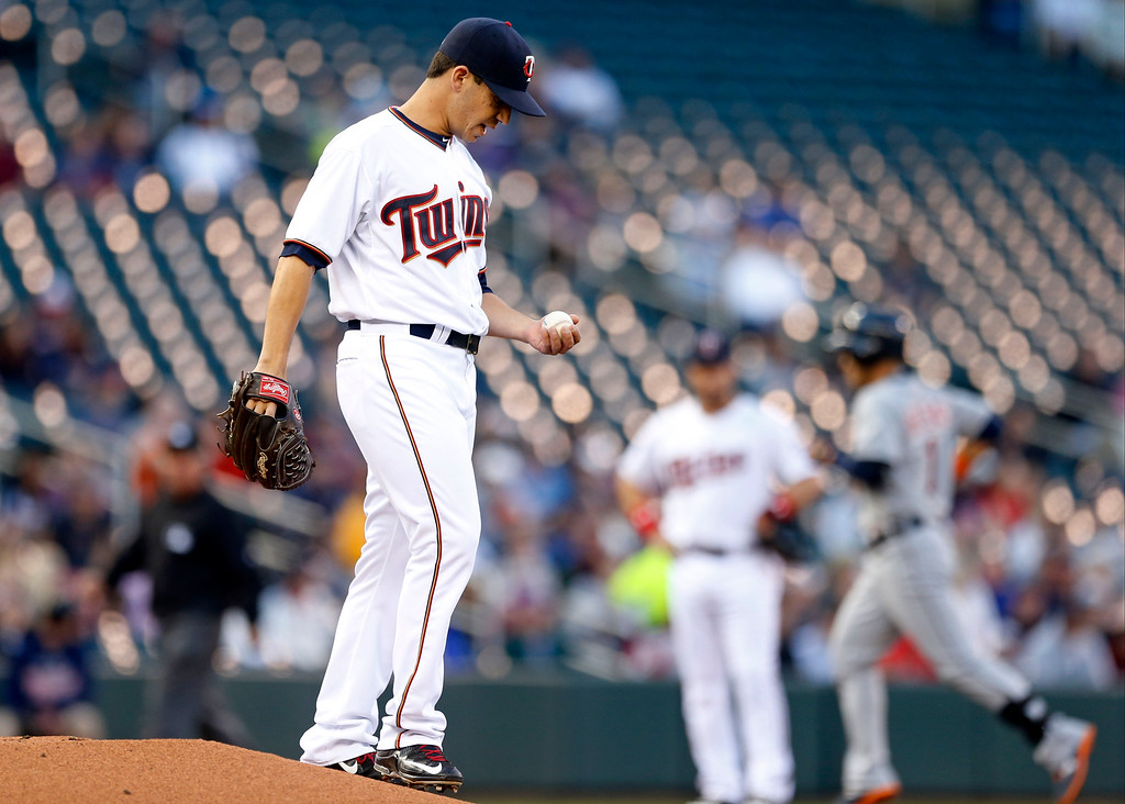 . Detroit Tigers� Jose Iglesias, right, rounds the bases on his solo home run off Minnesota Twins pitcher Tommy Milone, left, in the first inning of a baseball game, Monday, April 27, 2015, in Minneapolis. (AP Photo/Jim Mone)
