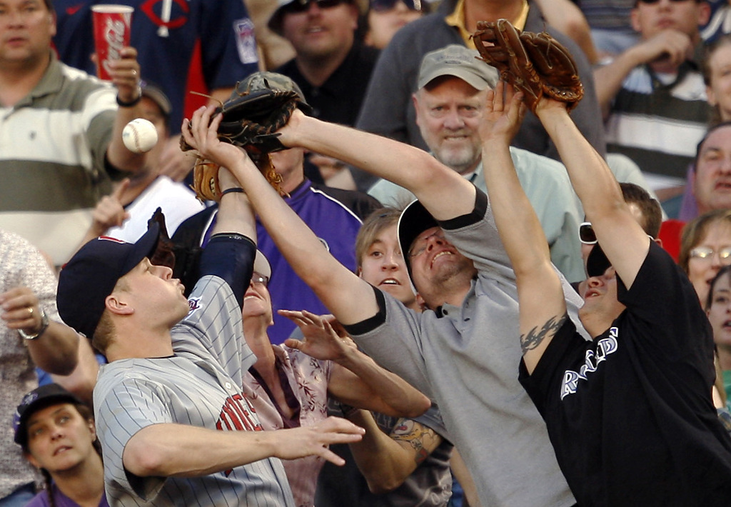 . Twins first baseman Justin Morneau, front, struggles to pull in a pop foul by Colorado\'s Matt Holliday as fans reach for the ball in the seventh inning of the Rockies\' 3-2 victory Saturday, May 17, 2008, in Denver. (AP Photo/David Zalubowski)