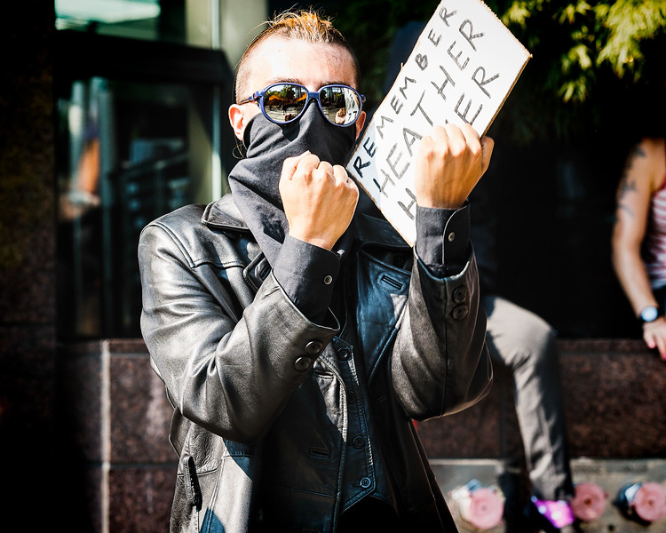 """An anti-fascist holds up his fists and a """"REMEMBER HEATHER HEYER"""" sign at far-right members gathered across the street at City Hall."""