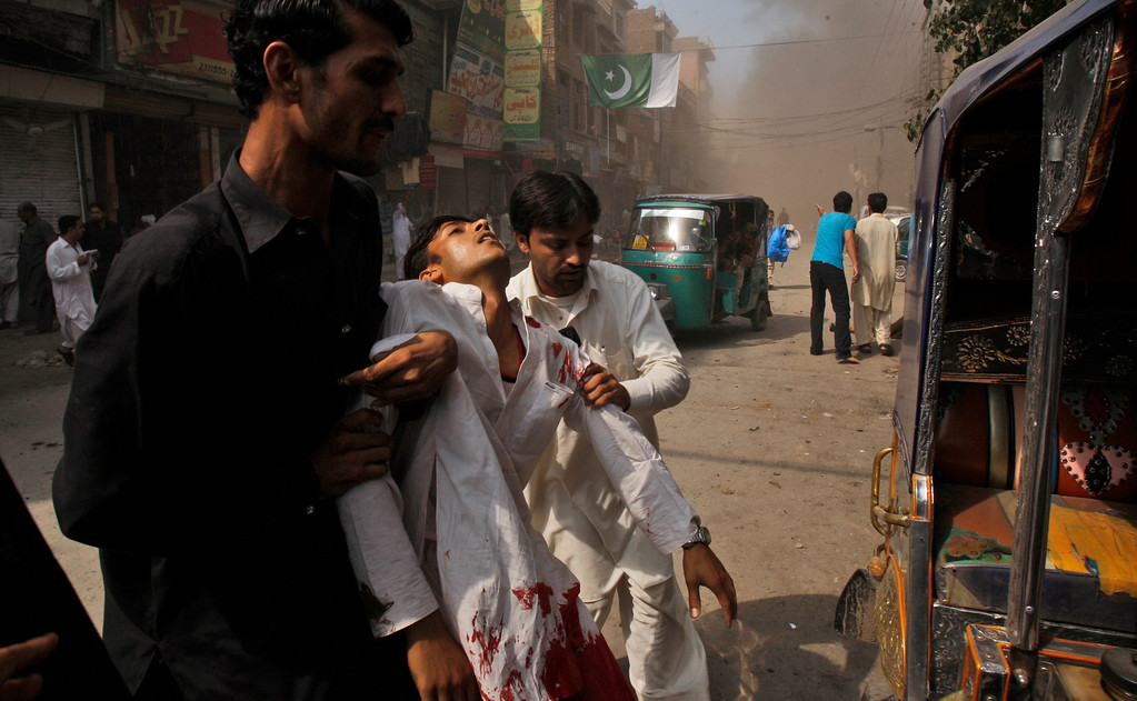 . Pakistani men help an injured man away from the site moments after a car bombing in Peshawar, Pakistan, Sunday, Sept. 29, 2013.  (AP Photo/Mohammad Sajjad)