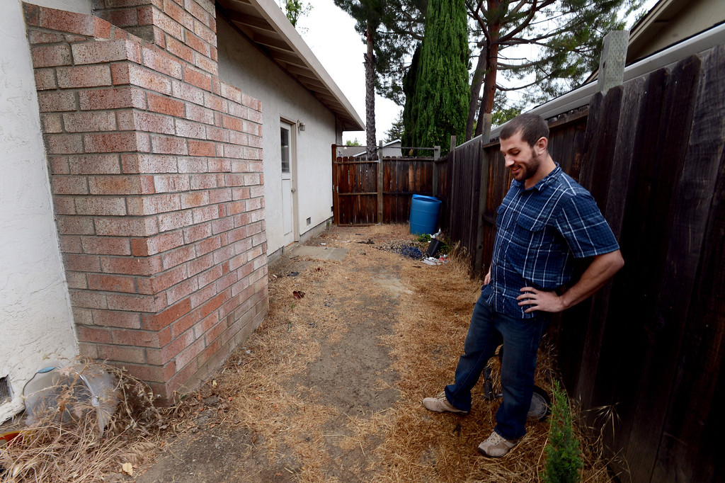 . Zach Grimm, owner of Kirby, 13, a cocker spaniel retriever mix, stands in his side yard in Concord, Calif., on Monday, June 24, 2013 where his dog was shot by a Concord Police Officer on June 17. Kirby was in the backyard while police were looking for a prowler. He barked at an officer that entered the yard and was shot. Grimm is angry at the police and says he would like an apology. (Susan Tripp Pollard/Bay Area News Group)
