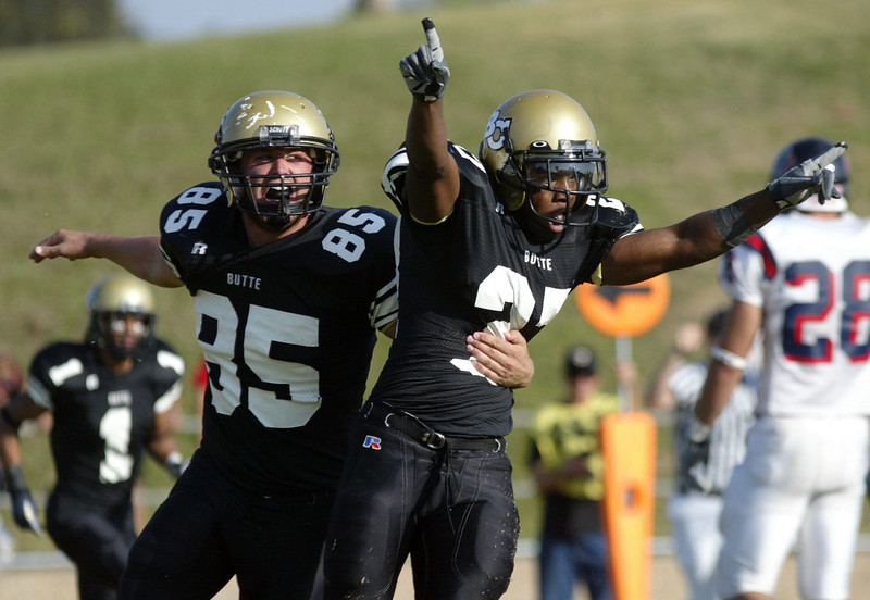 Butte College's #27 Shawn Overton (right) celebrates with #85 Robert Ruffing (left) after Overton leaped into the endzone for a touchdown against Santa Rosa putting the score (Butte:42-SantaRosa:35) in the fifth quarter (first OT) of thier football game at Cowan field Saturday. - halley photo 10/14/06