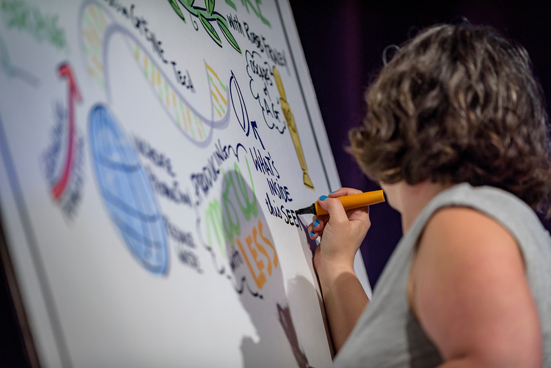 An artist from The Ink Factory draws an interpretation of a lecture given during the Dawn Or Doom conference in Fowler Hall. (Purdue University Photo/Alex Kumar)