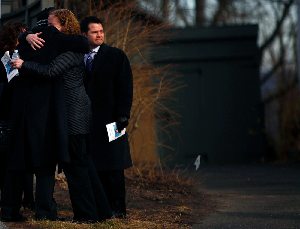 . People hug after the funeral of six-year-old Benjamin Wheeler who was killed December 14 in a deadly shooting at Sandy Hook Elementary school in Newtown, Connecticut, December 20, 2012. Even as they buried more victims of the second-deadliest school shooting in U.S. history on Thursday, residents of Newtown, Connecticut, looked for ways to pressure national leaders to restrict access to weapons. REUTERS/Eric Thayer