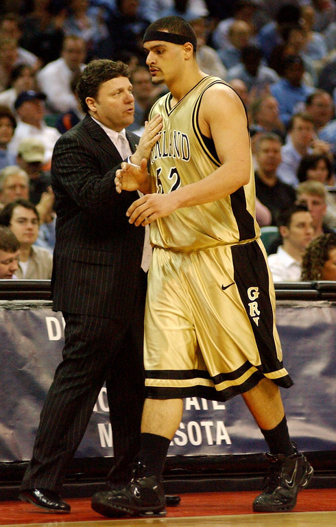 . Oakland University men\'s basketball head coach Greg Kampe, left, congratulates Cortney Scott for his efforts as Scott is taken out of the game during the final minutes of their game against North Carolina during first half action, Friday, March 18, 2005, at the Charlotte Coliseum in Charlotte, NC.  Oakland lost to North Carolina, 96-68.