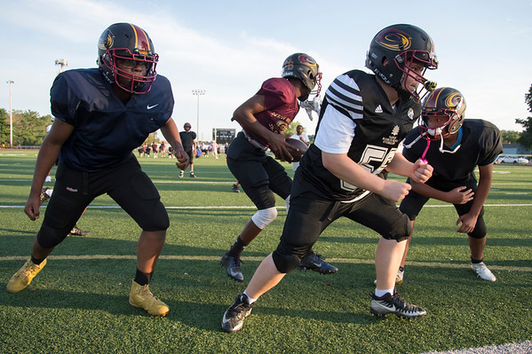 08/15/19 Wesley Bunnell | Staff Ife Olobroude , Julian Przecioska, and Louis Padilla run through drills with their team during the 13 year old Junior Hurricane Football practice at Chesley Park on Thursday August 15, 2019.