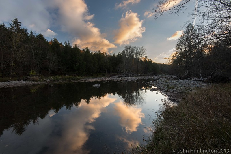 The sky reflected off a river in the catskills in the fall