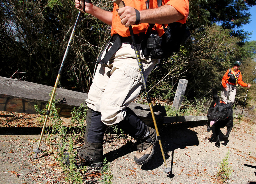 . Gerald Osuna, left, Kato, a two-year-old German shepherd cadaver rescue dog and Peg Thompson, of Santa Clara County Sheriff\'s Search and Rescue team, follow the trail during the search for the missing 22-month-old  Daphne Webb near Merritt College in Oakland, Calif., on Saturday, Aug. 24, 2013. Oakland police, along with Alameda County Sheriff and Santa Clara County Sheriff volunteer rescue teams and FBI agencies, searched for evidence of the Oakland child. (Ray Chavez/Bay Area News Group)